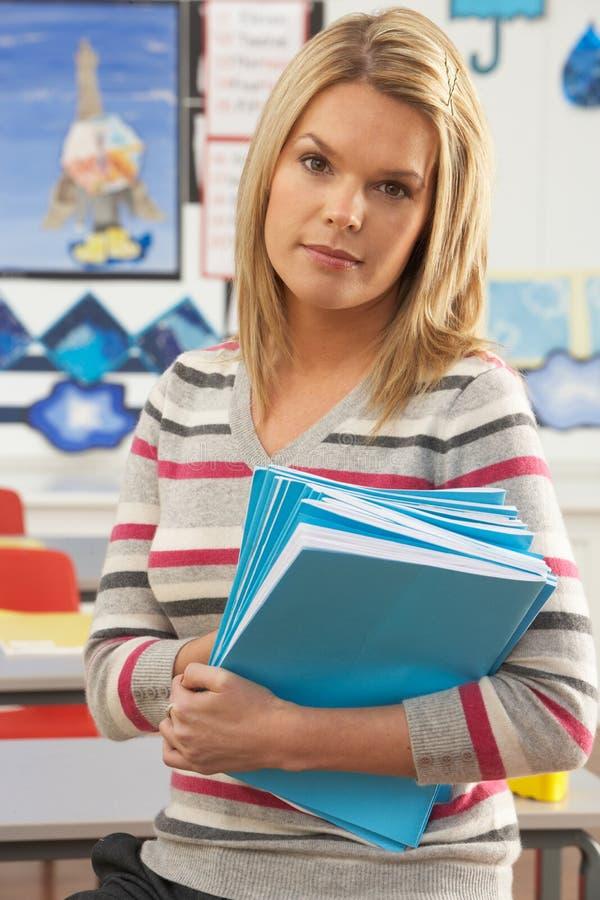 Weiblicher Lehrer, der am Schreibtisch im Klassenzimmer sitzt stockfoto