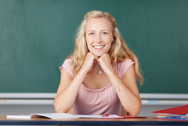 Weiblicher Lehrer With Hands On Chin Sitting At Desk stockfotos