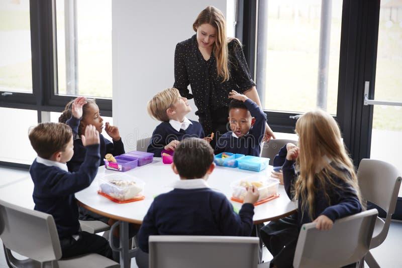 Weiblicher Lehrer steht, sprechend mit einer Gruppe Grundschulekindern, die zusammen an einem Rundtisch ihre Lunchpakete essend s lizenzfreies stockfoto