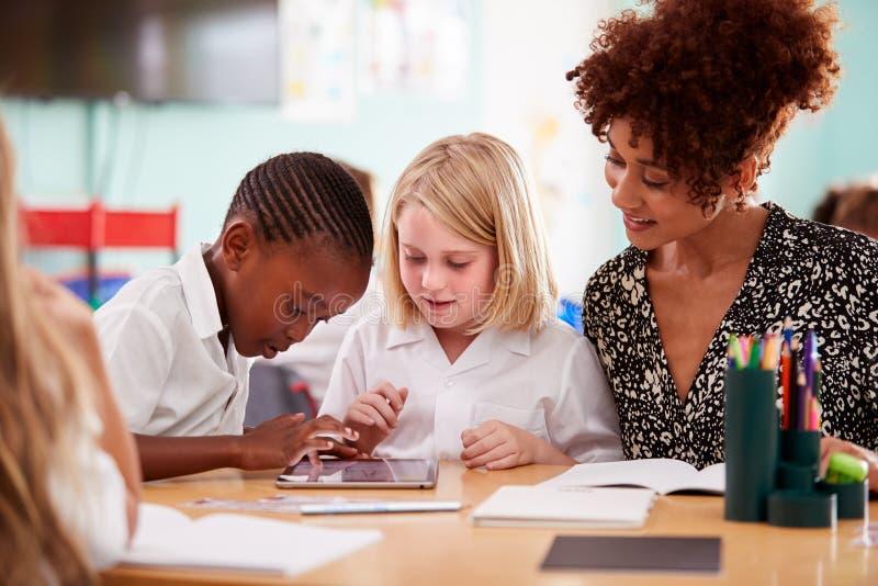 Weiblicher Lehrer-With Two Elementary-Schulschüler, die Uniform unter Verwendung Digital-Tablets am Schreibtisch tragen stockfotografie