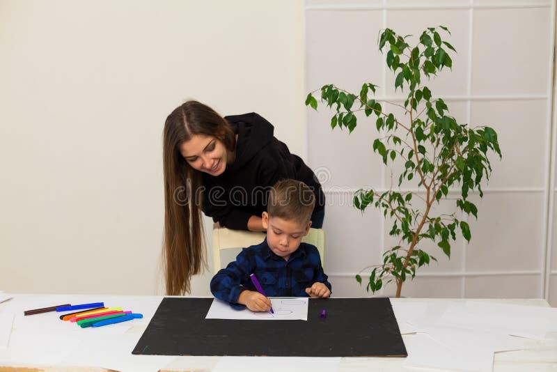 Weiblicher Lehrer unterrichtet einen kleinen Jungen, am Tisch zu zeichnen lizenzfreies stockbild