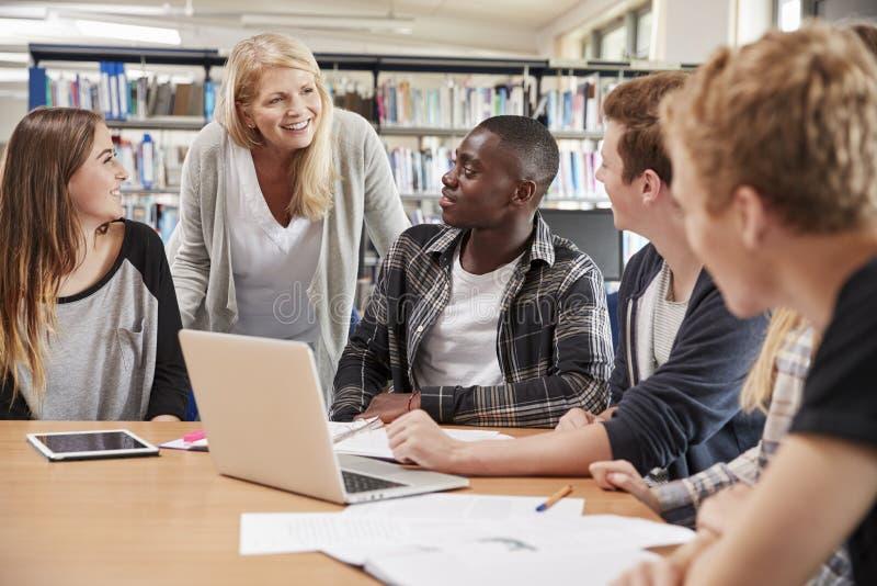 Weiblicher Lehrer-Working With College-Studenten in der Bibliothek stockbilder