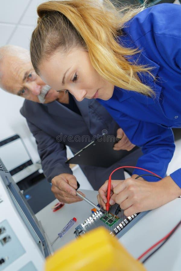 Weiblicher Lehrling mit Kalibrierungsausrüstung des Lehrers lizenzfreies stockfoto