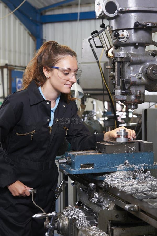 Weiblicher Lehrlings-Ingenieur Working On Drill in der Fabrik lizenzfreie stockfotos
