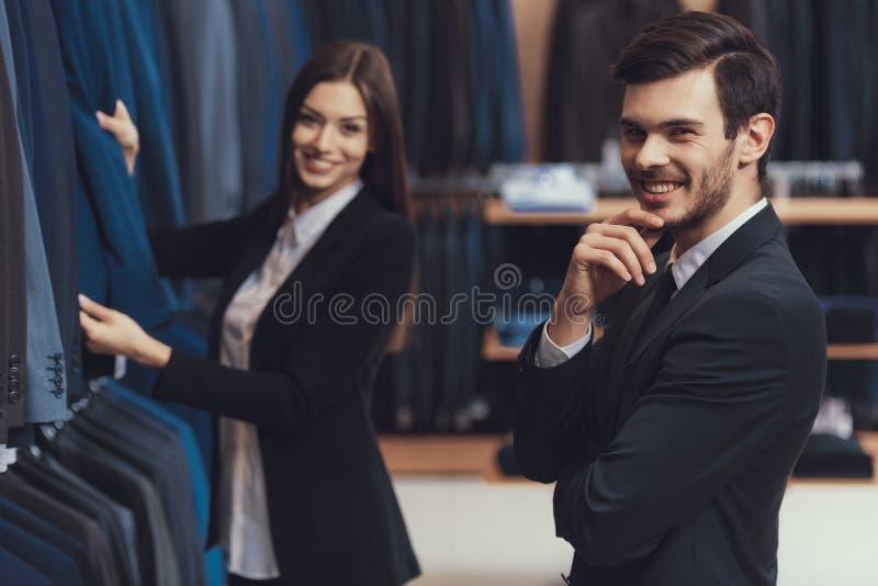 Weiblicher Männerkleidungsspeicherberater hilft, Jacke für jungen Mann im Anzug zu wählen lizenzfreie stockfotos