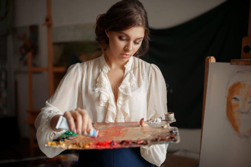 Weiblicher Maler f?gt Farbe der Palette im Studio hinzu lizenzfreies stockbild