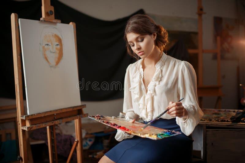 Weiblicher Maler hält Farbpalette und -bürste stockfotografie
