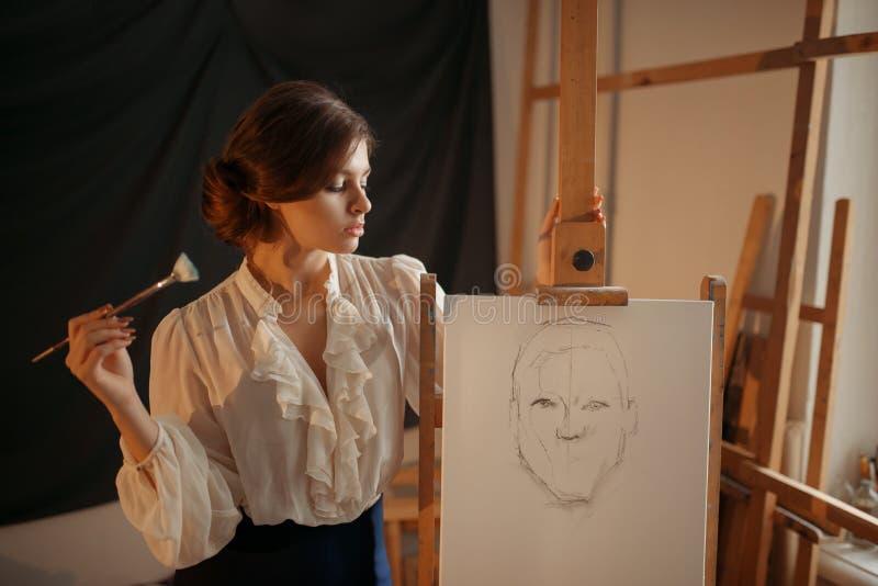 Weiblicher Maler mit B?rstenstellung gegen Gestell lizenzfreies stockbild