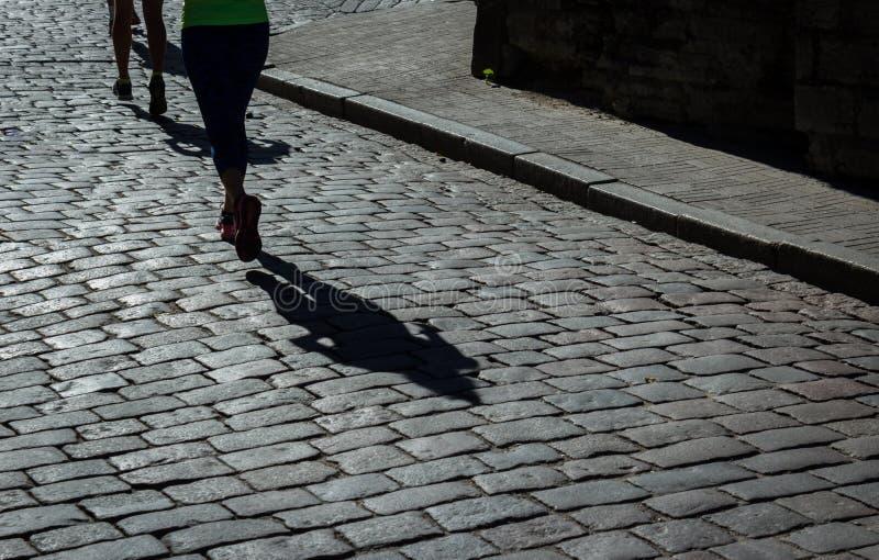 Weiblicher Marathonläufer und ihr Schatten auf cobblestoned Straße der Stadt stockfoto