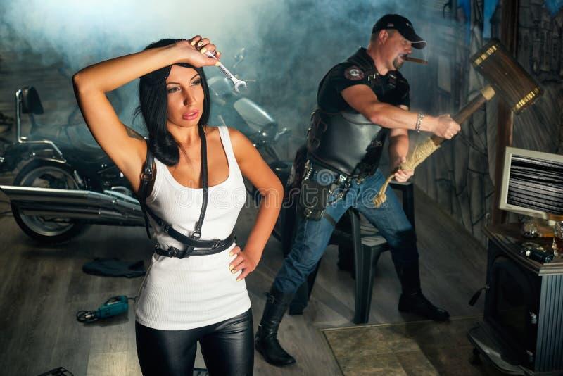 weiblicher Mechaniker, der mit seinem Mitarbeitermann steht lizenzfreies stockfoto