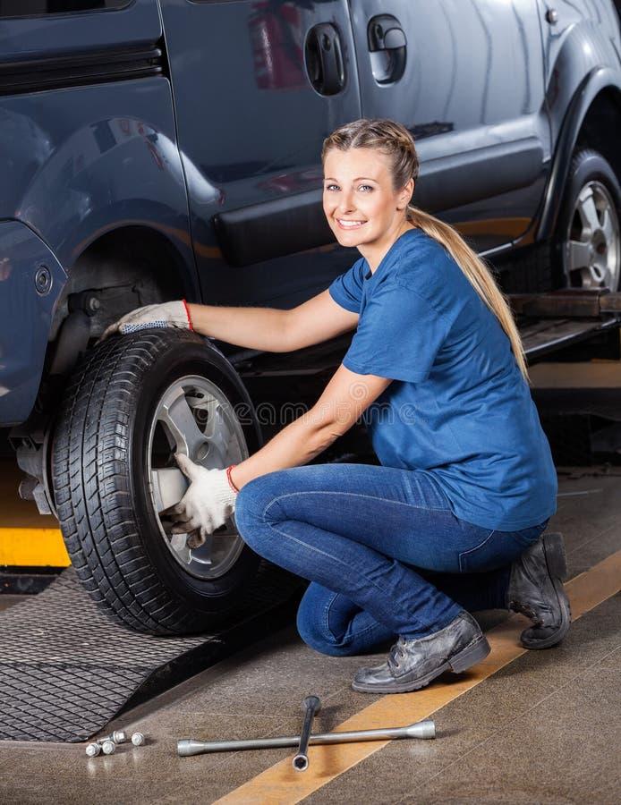 Weiblicher Mechaniker Fixing Car Tire lizenzfreie stockfotos