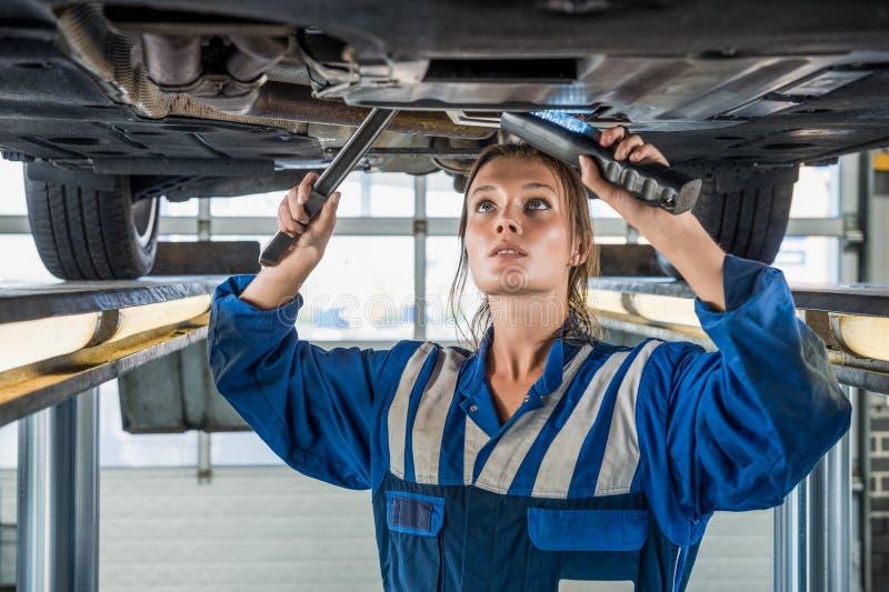 Weiblicher Mechaniker Using Flashlight While, das Auto auf Aufzug repariert stockbild