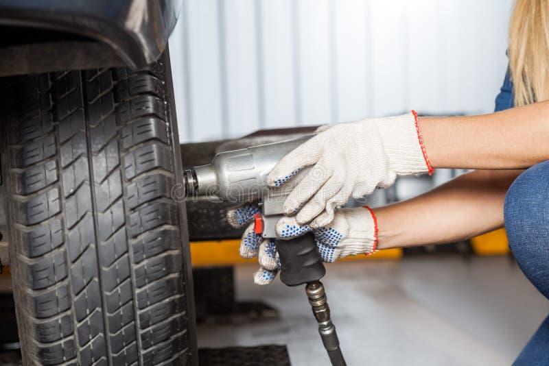 Weiblicher Mechaniker Using Pneumatic Wrench, zum des Reifens zu reparieren lizenzfreie stockfotos