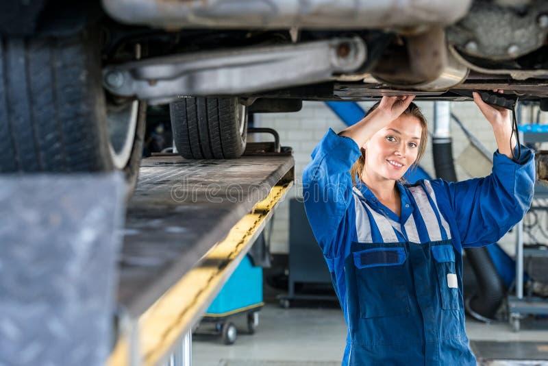 Weiblicher Mechaniker Working Under Car auf Hebebühne stockfotos