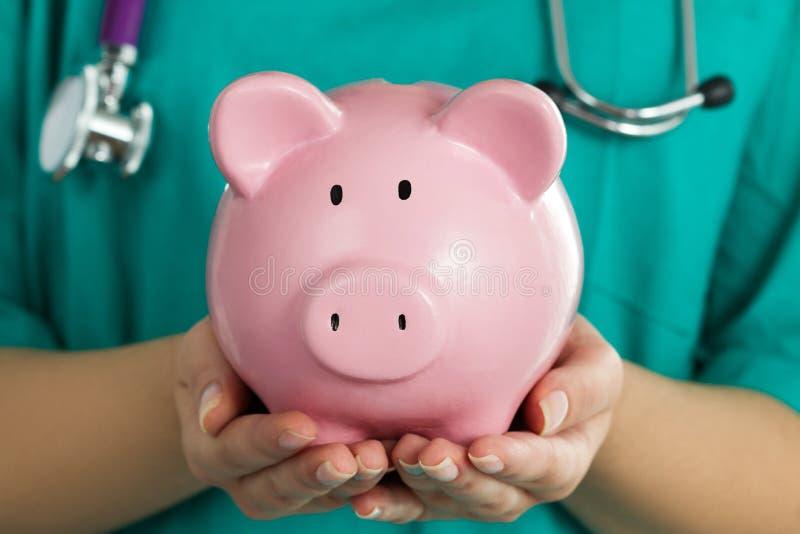 Weiblicher Medizindoktor, der Sparschwein hält lizenzfreie stockbilder