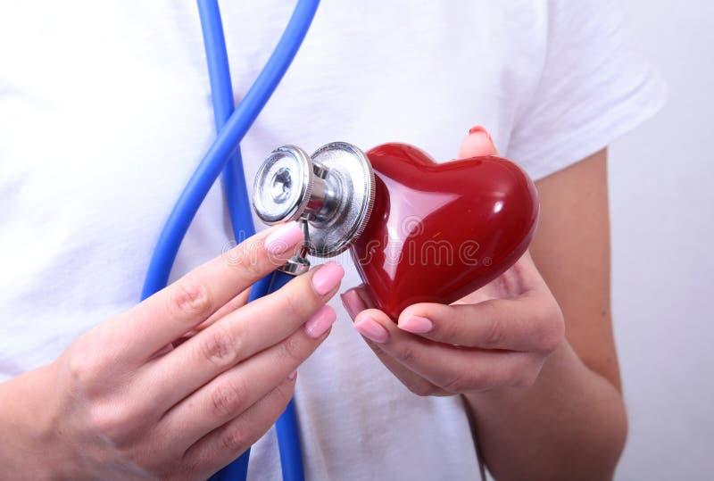 Weiblicher Medizindoktorgriff Handim roten Spielzeugherzen und Stethoskop gehen voran Herz Therapeutist, Studentenbildung lizenzfreies stockbild