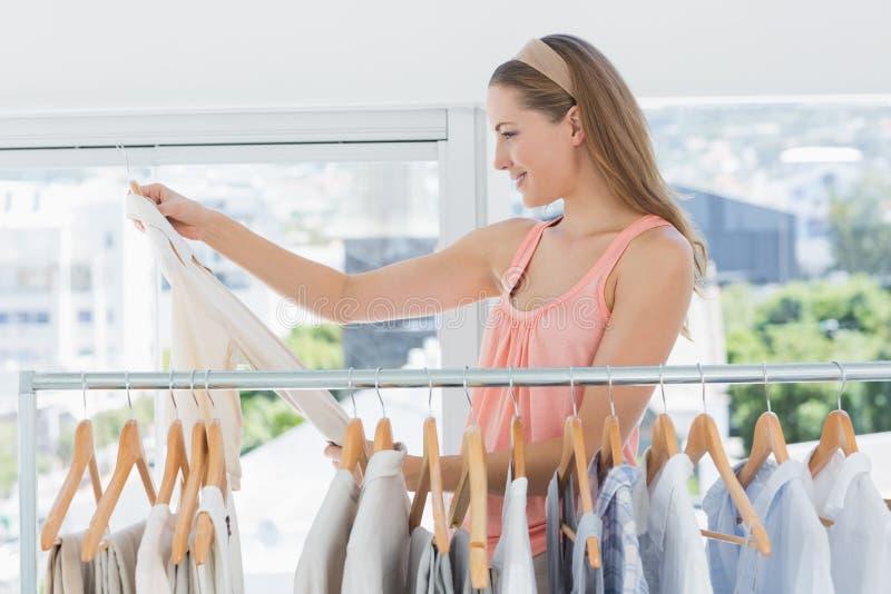 Weiblicher Modedesigner, der Hemd durch Gestell von Kleidung im Speicher betrachtet lizenzfreie stockbilder