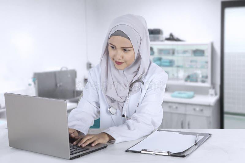 Weiblicher moslemischer Doktor arbeitet mit Laptop lizenzfreie stockbilder