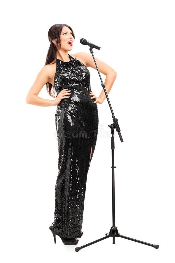 Weiblicher Musiker, der auf einem Mikrofon unterzeichnet stockfoto