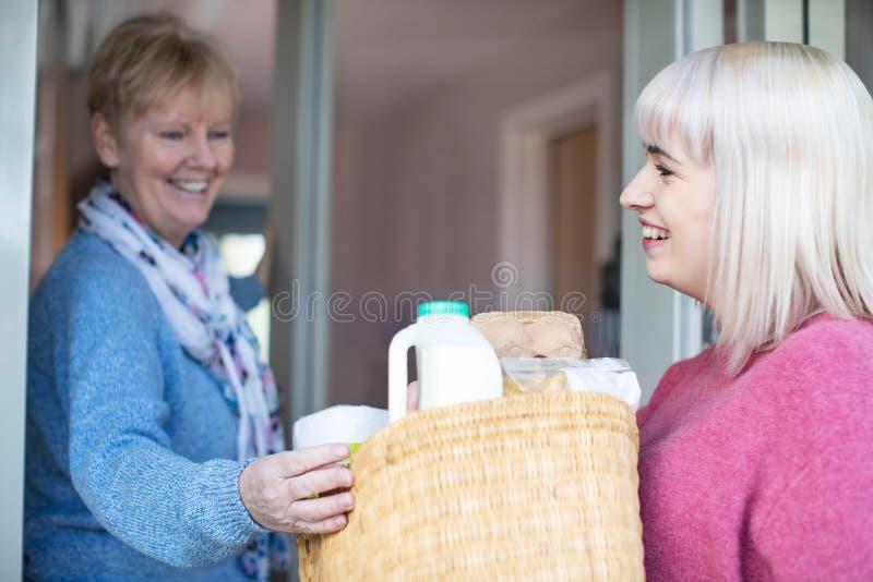 Weiblicher Nachbar, welche ?lterer Frau mit dem Einkaufen hilft lizenzfreies stockfoto
