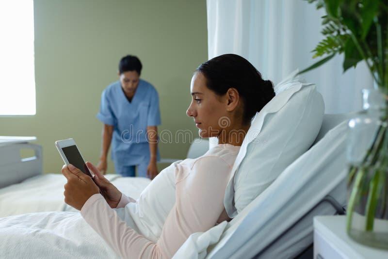 Weiblicher Patient, der digitale Tablette im Bezirk am Krankenhaus verwendet lizenzfreies stockfoto