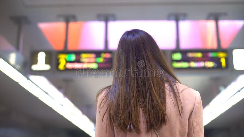 Weiblicher Pendler, der Zeitplan auf dem Bahnhof, touristisch in der neuen Stadt betrachtet lizenzfreies stockbild