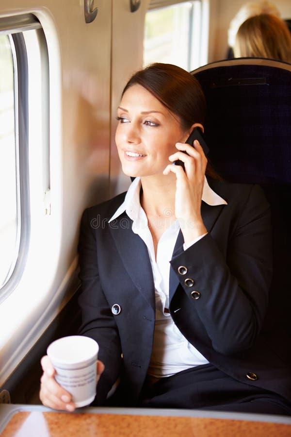 Weiblicher Pendler mit Kaffee auf Zug unter Verwendung des Handys lizenzfreies stockfoto