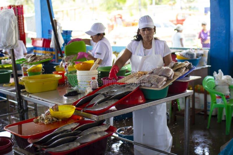 Weiblicher peruanischer Verk?ufer an einem Fischmeeresfr?chtemarkt lizenzfreies stockbild