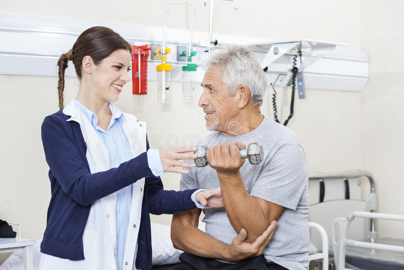 Weiblicher Physiotherapeut Assisting Senior Man, zum des Dummkopfs anzuheben stockfotos