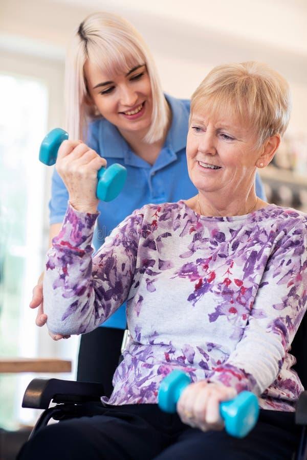 Weiblicher Physiotherapeut Helping Senior Woman im Rollstuhl, zum von Handgewichten anzuheben stockfoto