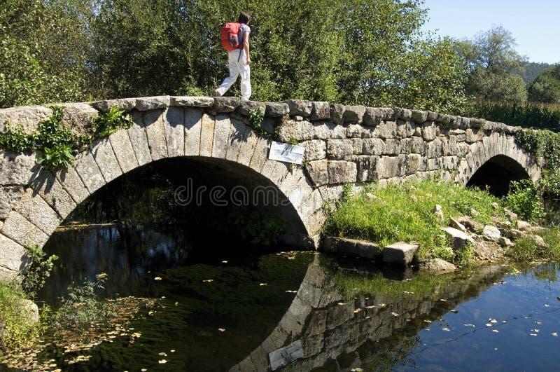 Weiblicher Pilger geht auf historische Brücke, Portugal lizenzfreie stockfotos