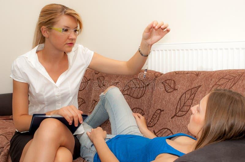 Weiblicher Psychotherapeut hypnotizes einen weiblichen Patienten lizenzfreies stockbild