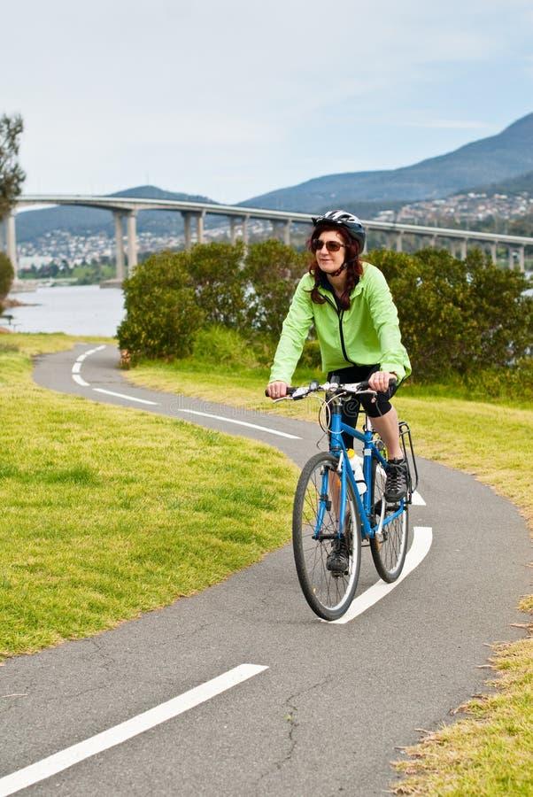 Weiblicher Radfahrer auf s-Schlaufe des Schleifepfades lizenzfreie stockfotografie