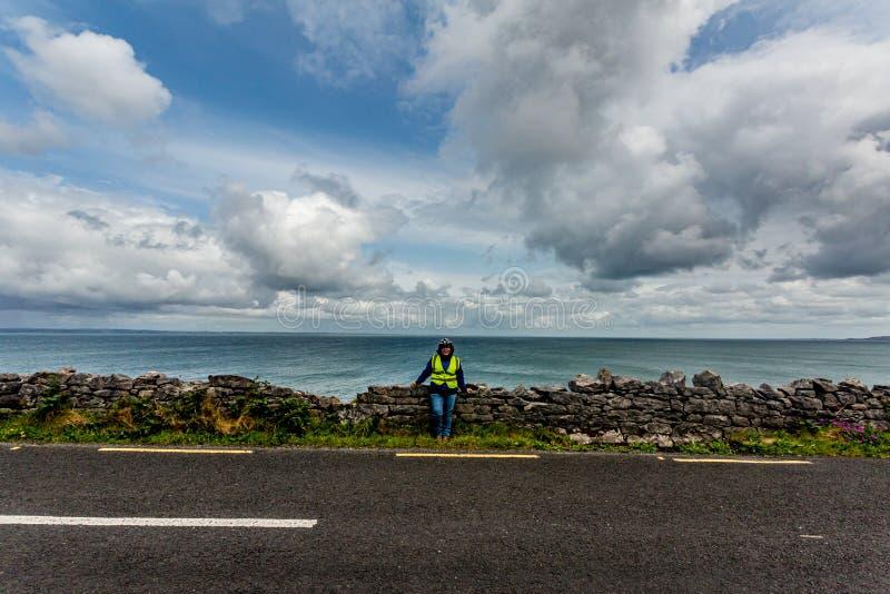 Weiblicher Radfahrer, der einen Bruch auf der Küsten-Straße R477 hat lizenzfreies stockfoto