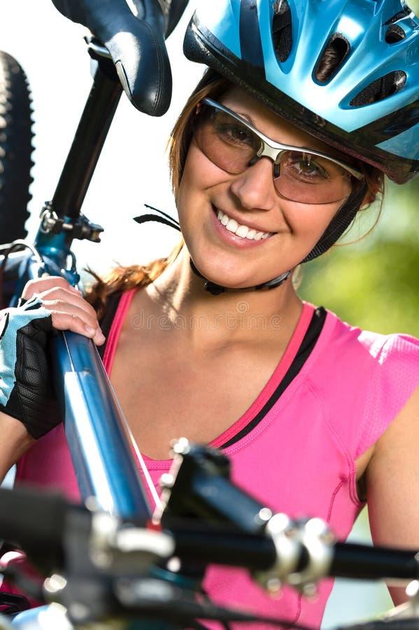 Weiblicher Radfahrer, der ihr Fahrrad trägt lizenzfreie stockfotografie