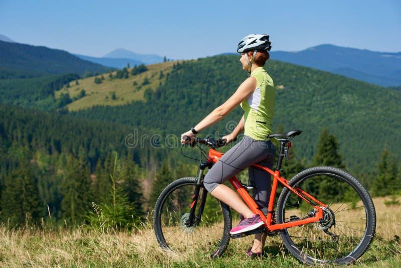Weiblicher Radfahrer im Sturzhelm, der mit rotem Fahrrad auf grasartigem Hügel steht stockfotos