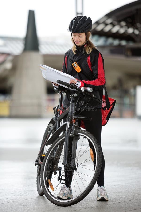 Weiblicher Radfahrer mit Kurier Bag And Package an lizenzfreies stockbild