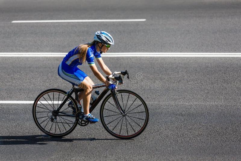 Weiblicher Radfahrer reitet ein laufendes Fahrrad auf Straße lizenzfreie stockfotografie
