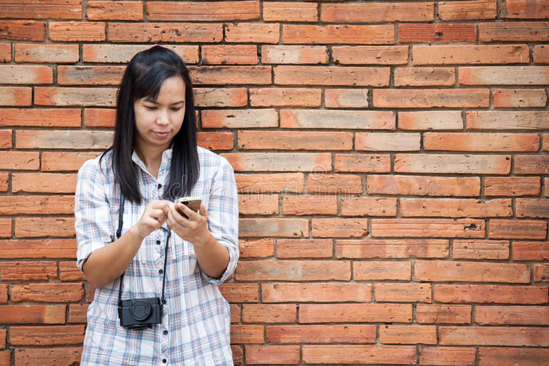 Weiblicher Reisender, der Smartphone mit Backsteinmauerhintergrund verwendet stockbild