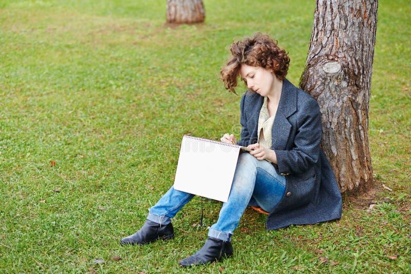 Weiblicher RothaarigeKunststudent, der draußen zeichnet lizenzfreie stockfotos