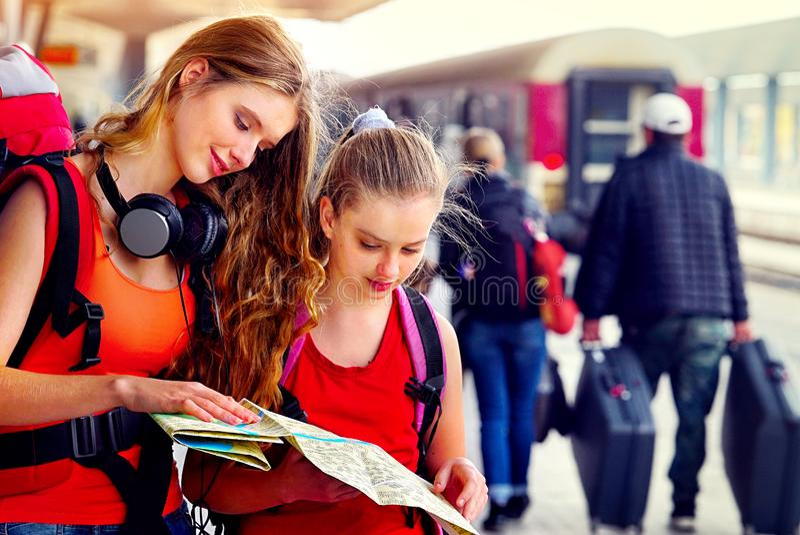 Weiblicher Rucksack des Reisendmädchens und Tourismusausstattung am Bahnhof stockfotografie