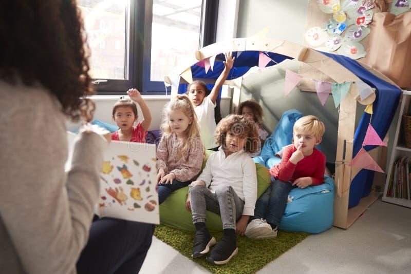 Weiblicher Säuglingsschullehrer, der auf einem Stuhl zeigt einer Gruppe Kindern ein Buch sitzen auf Bohnentaschen in einer bequem lizenzfreie stockbilder