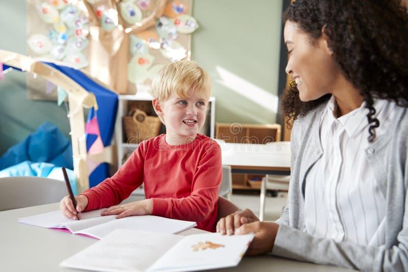 Weiblicher Säuglingsschullehrer, der ein auf einem mit einem jungen weißen Schüler, sitzend an einem Tisch in einem Klassenzimmer lizenzfreie stockfotos