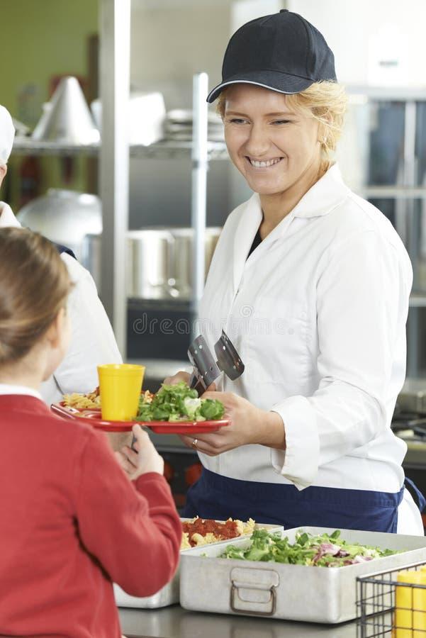 Weiblicher Schüler in der Schulcafeteria, die das Mittagessen durch Abendessen-La gedient wird stockfotografie