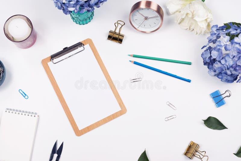 Weiblicher Schreibtischarbeitsplatzrahmen mit Schönheitsanordnung für Blumenstraußhortensien, Klemmbrett, Kaffeetasse, Klipp, Uhr lizenzfreie stockfotos