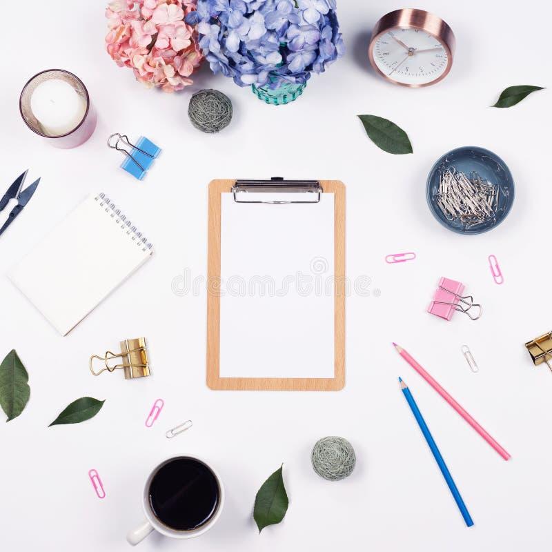 Weiblicher Schreibtischarbeitsplatzrahmen mit Schönheitsanordnung für Blumenstraußhortensien, -klemmbrett, -notizbuch, -clip, -uh stockfotografie