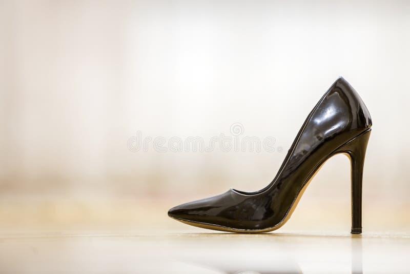 Weiblicher Schuh des modernen Ausschnitts des hohen Absatzes ledernen schwarzen mit den goldenen Schnallen lokalisiert auf hellem lizenzfreie stockbilder