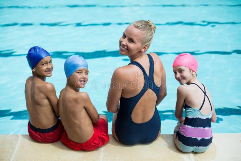 Weiblicher Schwimmenlehrer mit den Studenten, die am Poolside sitzen lizenzfreie stockfotos