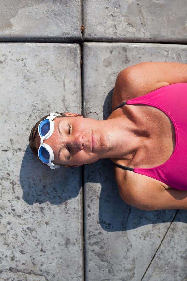 Weiblicher Schwimmer, der am Poolrand liegt stockbild