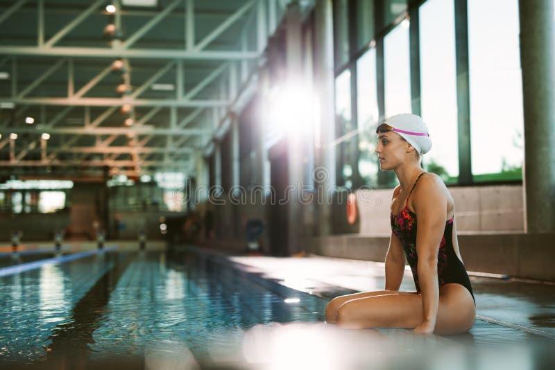 Weiblicher Schwimmer, der am Rand eines Pools sich entspannt stockfoto